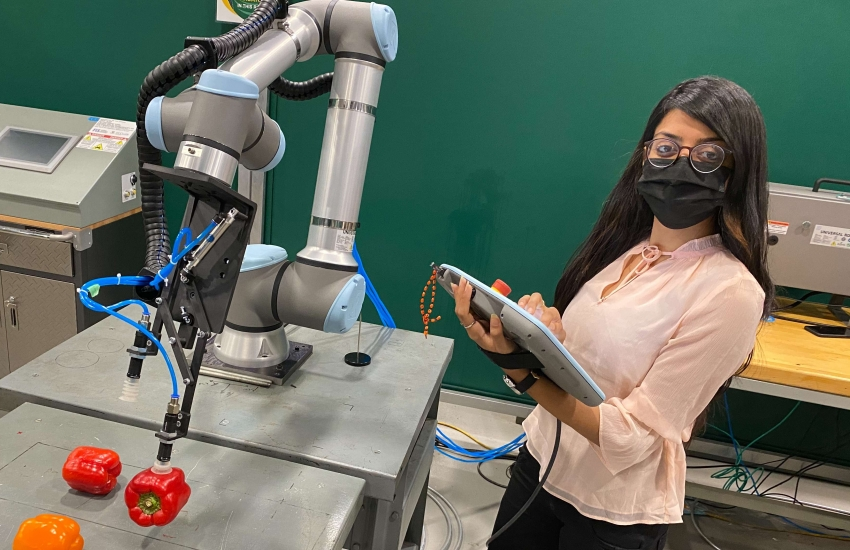 Khushboo Patel holds the controller she uses to direct the Universal Robotics UR10 collaborative robot.