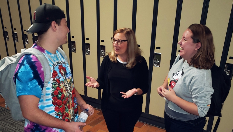 Social Justice and Legal Studies Professor Joyce Zuk talks to students Armand Avolio and Samantha Elford